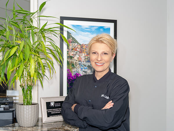 Dr. Laura Liutkiene smiling standing while wearing her black dentist uniform