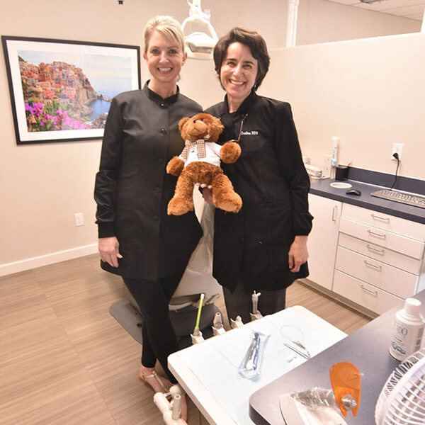 Two of our female dental assistants inside the surgery room holding a teddy bear while smiling