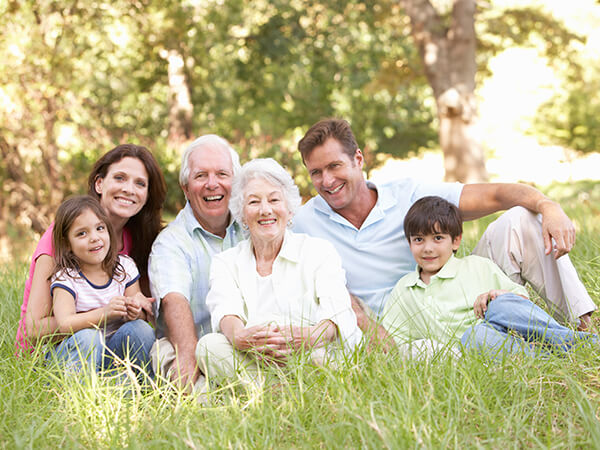 A family of parents and two grandparents sitting on the grass in a park while smiling and hugging