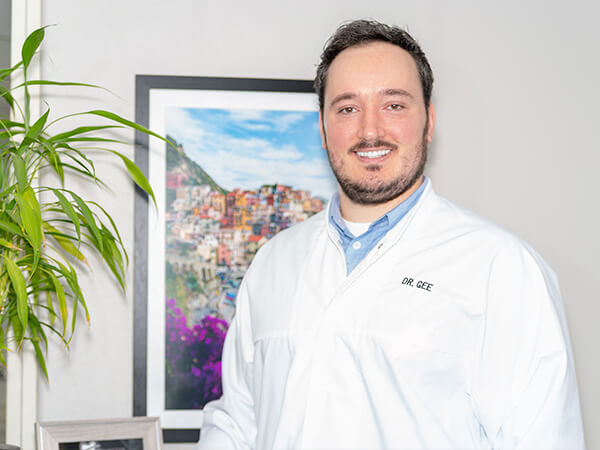 Dr. Gee, one of our dentists, standing next to a green plant smiling in his white coat
