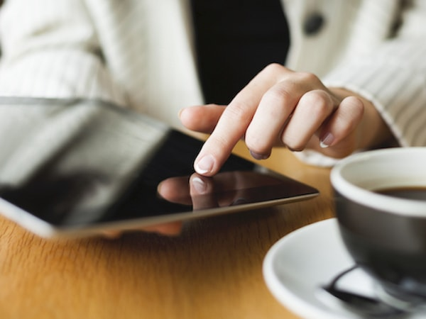 Close up of someone using a tablet next to a black coffee