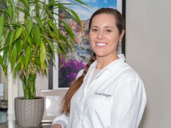 One of our dentists, Dr. Laura Burgett wearing white overalls and smiling at the reception desk