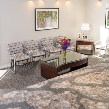 Dental waiting room featuring chairs and table with fresh flowers