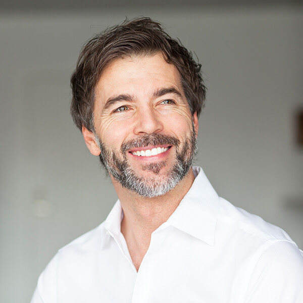 A mature man with white shirt, beard, and black hair ready for his restorative dentistry treatment