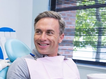 Mature man sitting in a dental chair looking to the right as he waits enjoy our services