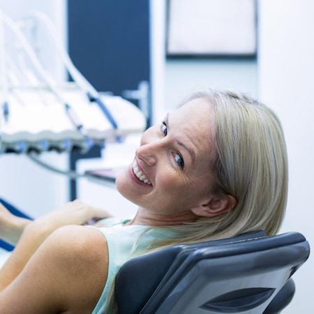 Woman laying on a dental treatment chair as she waits to receive family dentistry