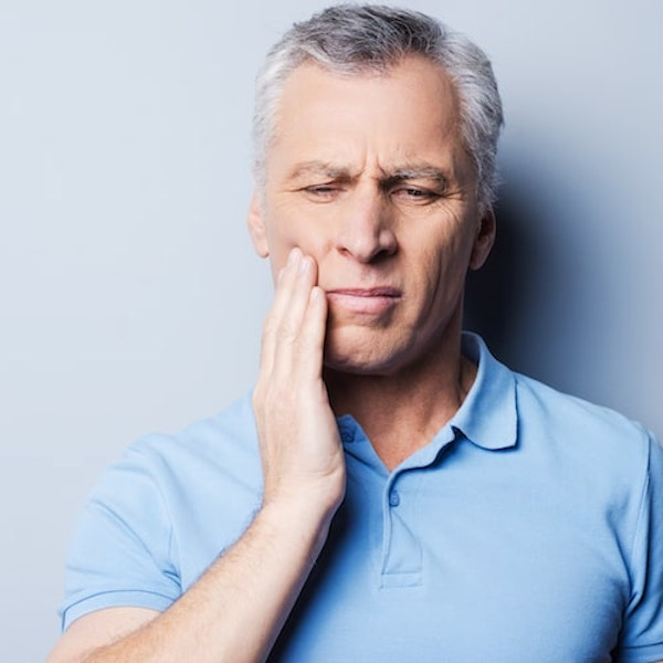 A man in a light blue top holding the side of his face in pain
